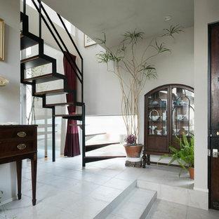 横浜の中サイズの片開きドアアジアンスタイルのおしゃれな玄関ホール (白い壁、磁器タイルの床、濃色木目調のドア、白い床) の写真