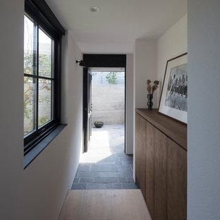 東京23区の片開きドアラスティックスタイルのおしゃれな玄関 (白い壁、黒いドア) の写真