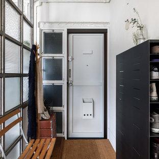 他の地域の片開きドアインダストリアルスタイルのおしゃれな玄関ホール (白い壁、無垢フローリング、白いドア、茶色い床) の写真
