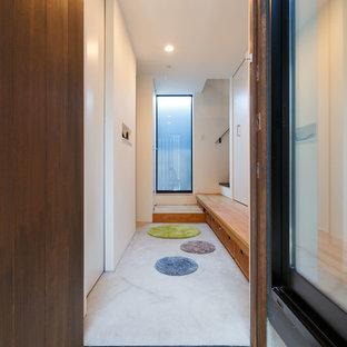 東京23区の片開きドアモダンスタイルのおしゃれな玄関ホール (茶色い壁、濃色木目調のドア、グレーの床) の写真