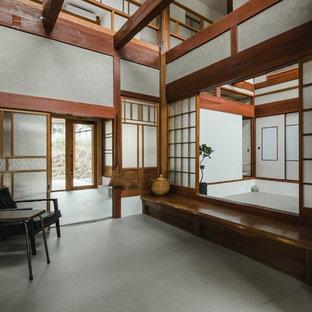 他の地域の巨大な引き戸和風のおしゃれな玄関ホール (グレーの壁、コンクリートの床、グレーの床、木目調のドア) の写真