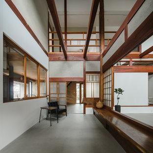 Esempio di un ampio corridoio etnico con pareti bianche, pavimento in cemento, una porta scorrevole, una porta in legno bruno e pavimento grigio