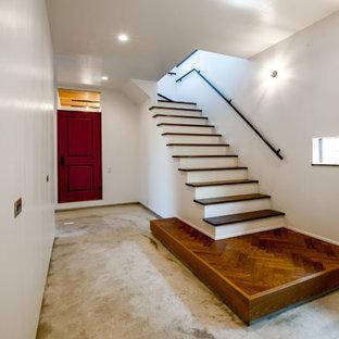 他の地域の片開きドアトラディショナルスタイルのおしゃれな玄関 (白い壁、黒いドア、コンクリートの床、グレーの床) の写真
