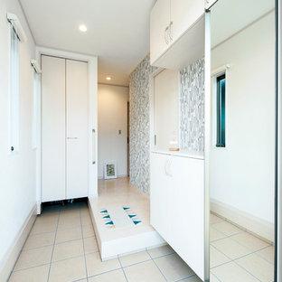 他の地域の北欧スタイルのおしゃれな玄関ホール (白い壁、ベージュの床) の写真