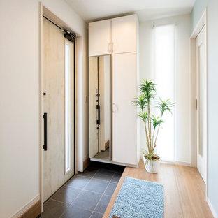 Modelo de entrada marinera, pequeña, con paredes blancas, puerta simple, puerta de madera clara y suelo negro