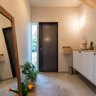 東京都下の片開きドアコンテンポラリースタイルのおしゃれな玄関 (白い壁、コンクリートの床、黒いドア、グレーの床) の写真