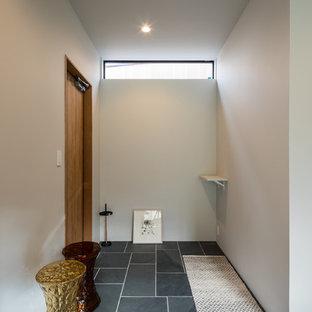 他の地域の片開きドアコンテンポラリースタイルのおしゃれな玄関ホール (茶色い壁、木目調のドア、黒い床) の写真