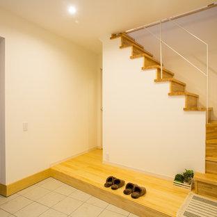 他の地域の引き戸カントリー風おしゃれな玄関 (白い壁、濃色木目調のドア、グレーの床) の写真