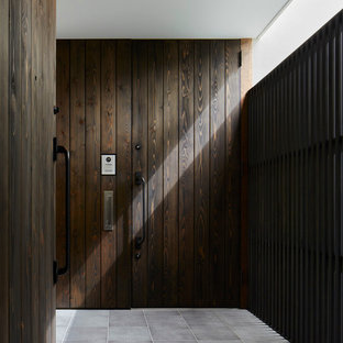 Foto de entrada urbana con paredes marrones, puerta simple y puerta de madera oscura