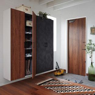 Immagine di un ingresso o corridoio industriale con pareti bianche, pavimento in legno massello medio, una porta singola, una porta in legno bruno e pavimento marrone