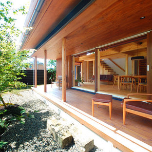 This is an example of a large zen side porch design in Other with a roof extension.