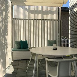 Immagine di un piccolo patio o portico con pannellatura minimalista davanti casa con piastrelle e una pergola