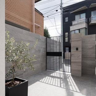 Ispirazione per un grande portico etnico davanti casa con piastrelle