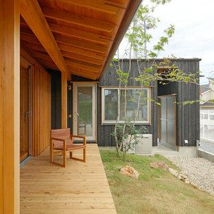 Idée de décoration pour un grand porche asiatique avec une terrasse en bois et une extension de toiture.