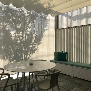 Idee per un piccolo patio o portico con pannellatura moderno davanti casa con piastrelle e una pergola