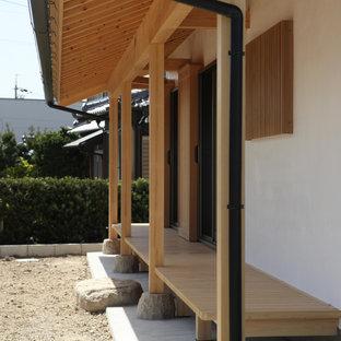 Esempio di un portico etnico di medie dimensioni e davanti casa con un tetto a sbalzo e parapetto in legno