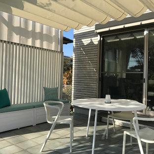 Foto di un piccolo patio o portico con pannellatura moderno davanti casa con piastrelle e una pergola