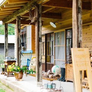 Foto di un piccolo portico country davanti casa con un portico chiuso, pavimentazioni in cemento e un tetto a sbalzo