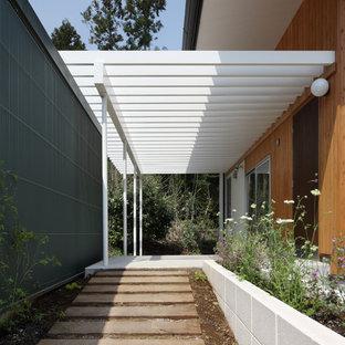 Ispirazione per un portico minimalista davanti casa con pavimentazioni in cemento e una pergola