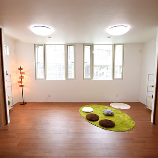 Minimalist gender-neutral plywood floor and brown floor nursery photo in Other with white walls