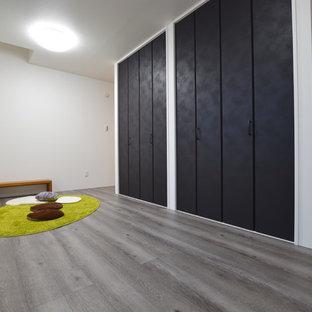 Cette image montre une chambre de bébé neutre minimaliste avec un mur blanc, un sol en contreplaqué et un sol gris.