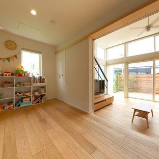 Imagen de habitación de bebé neutra papel pintado, nórdica, de tamaño medio, con paredes blancas, suelo de madera clara, suelo marrón, papel pintado y papel pintado