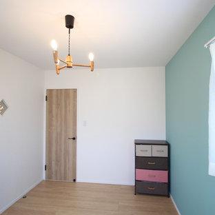 Skandinavisk inredning av ett könsneutralt babyrum, med flerfärgade väggar, plywoodgolv och beiget golv
