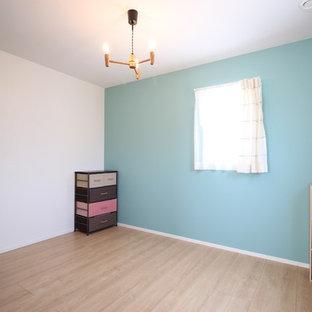 Cette photo montre une chambre de bébé neutre avec un mur multicolore, un sol en contreplaqué et un sol beige.