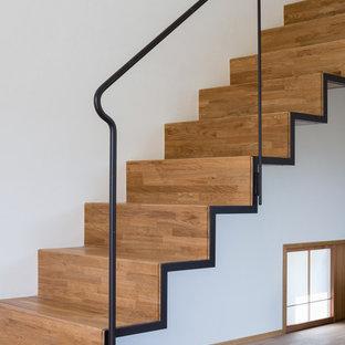 Modelo de escalera suspendida, minimalista, de tamaño medio, con escalones de madera, contrahuellas de madera y barandilla de metal