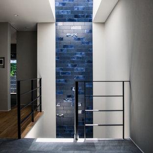 Diseño de escalera curva y papel pintado, moderna, de tamaño medio, con barandilla de metal y papel pintado