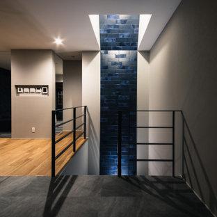 Ejemplo de escalera curva y papel pintado, moderna, de tamaño medio, con barandilla de metal y papel pintado