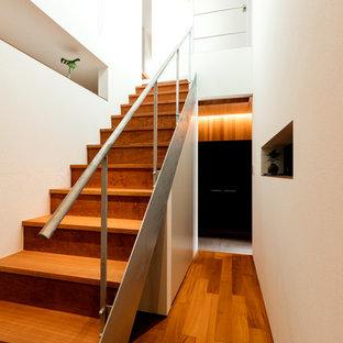 他の地域の中サイズの木のモダンスタイルのおしゃれな階段 (木の蹴込み板、金属の手すり) の写真