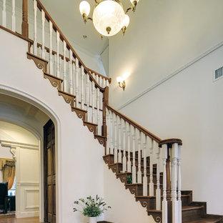 Immagine di una grande scala classica con pedata in marmo e alzata in legno