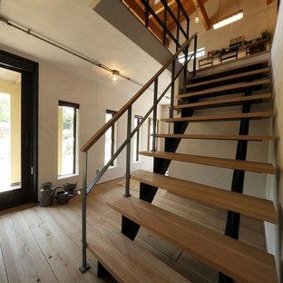 他の地域の中くらいの木のインダストリアルスタイルのおしゃれな階段 (混合材の手すり) の写真