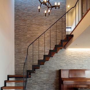 Foto de escalera en L, de estilo zen, sin contrahuella, con escalones de madera y barandilla de metal