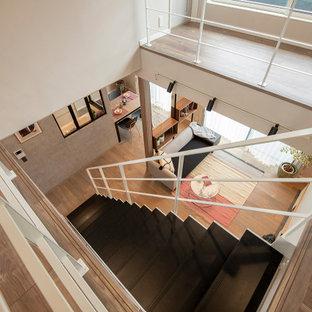 Ejemplo de escalera recta y panelado, minimalista, de tamaño medio, sin contrahuella, con escalones de madera, barandilla de metal y panelado