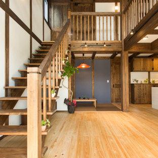 Foto di una grande scala a rampa dritta etnica con pedata in legno e nessuna alzata
