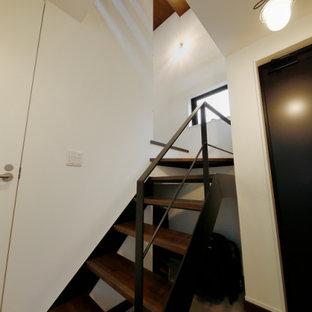 Foto de escalera en U y papel pintado, industrial, pequeña, sin contrahuella, con escalones de madera, barandilla de metal y papel pintado