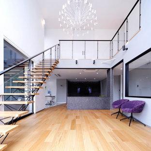 На фото: большая прямая лестница в стиле лофт с деревянными ступенями, стеклянными перилами и обоями на стенах без подступенок с