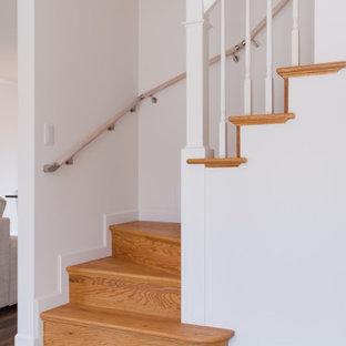 他の地域の広い木のトラディショナルスタイルのおしゃれなかね折れ階段 (木の蹴込み板、木材の手すり、壁紙) の写真