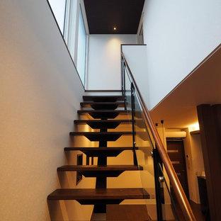 Ejemplo de escalera suspendida, sin contrahuella, con escalones de madera pintada y barandilla de vidrio