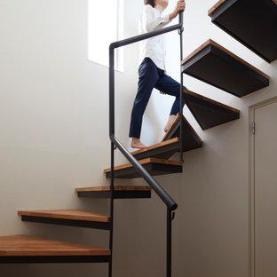 Foto de escalera curva y papel pintado, minimalista, de tamaño medio, sin contrahuella, con escalones de madera, barandilla de metal y papel pintado