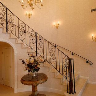 Imagen de escalera curva y papel pintado, tradicional, con escalones de mármol, contrahuellas de mármol, barandilla de metal y papel pintado