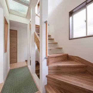 Idée de décoration pour un petit escalier droit nordique avec des marches en bois, un garde-corps en bois et du papier peint.