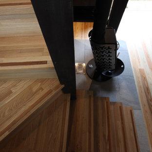 """Immagine di una scala a """"L"""" etnica di medie dimensioni con pedata in legno, alzata in legno, parapetto in legno e carta da parati"""