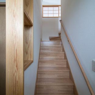 Diseño de escalera en U y papel pintado con escalones de madera, contrahuellas de madera, barandilla de madera y papel pintado