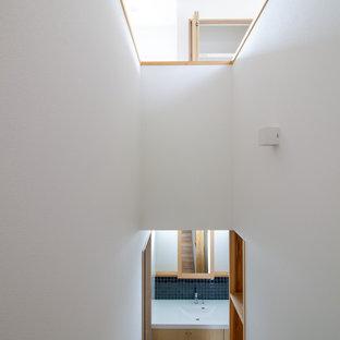 Imagen de escalera en U y papel pintado con escalones de madera, contrahuellas de madera, barandilla de madera y papel pintado