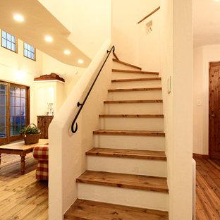 他の地域の木のカントリー風おしゃれなサーキュラー階段 (金属の手すり) の写真