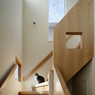 東京23区の小さい木のモダンスタイルのおしゃれなかね折れ階段 (木の蹴込み板、木材の手すり) の写真