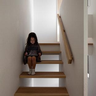 Foto de escalera suspendida, actual, pequeña, sin contrahuella, con escalones de madera y barandilla de madera